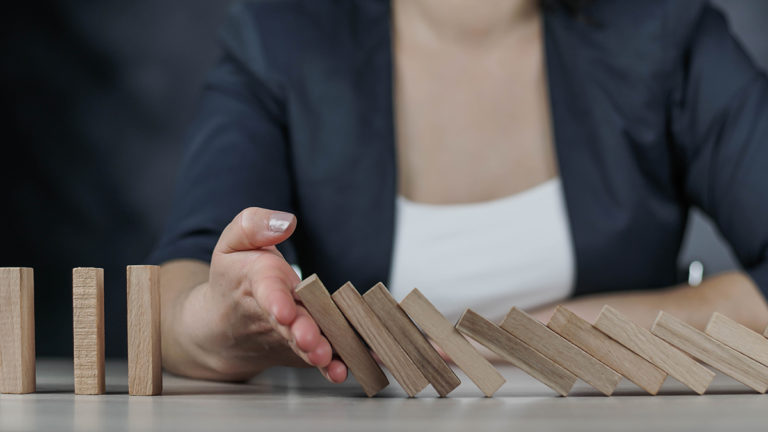 Business woman using her hand to stop the domino effect of fallen wooden blocks signifies the prevention of continued impacts of systems downtime by having a business continuity and disaster recovery plan in-place.