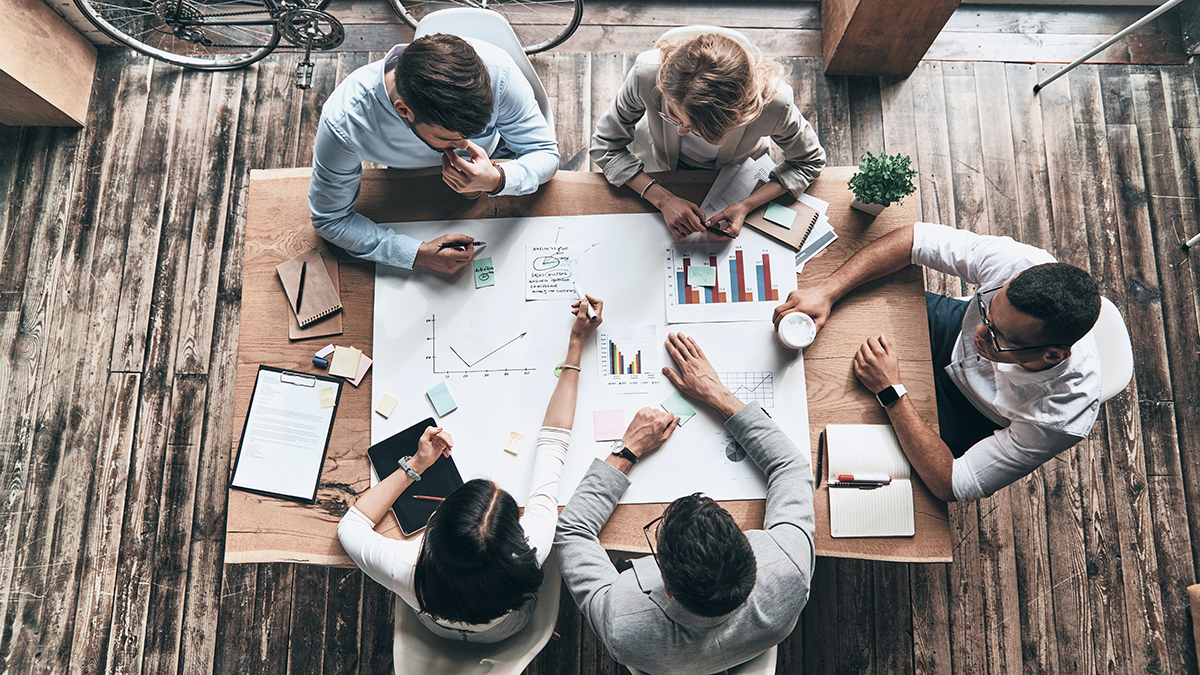 Passionate about their small business project. Top view of young modern people in smart casual wear working with presentation materials while sitting around a wooden conference table in a creative office.