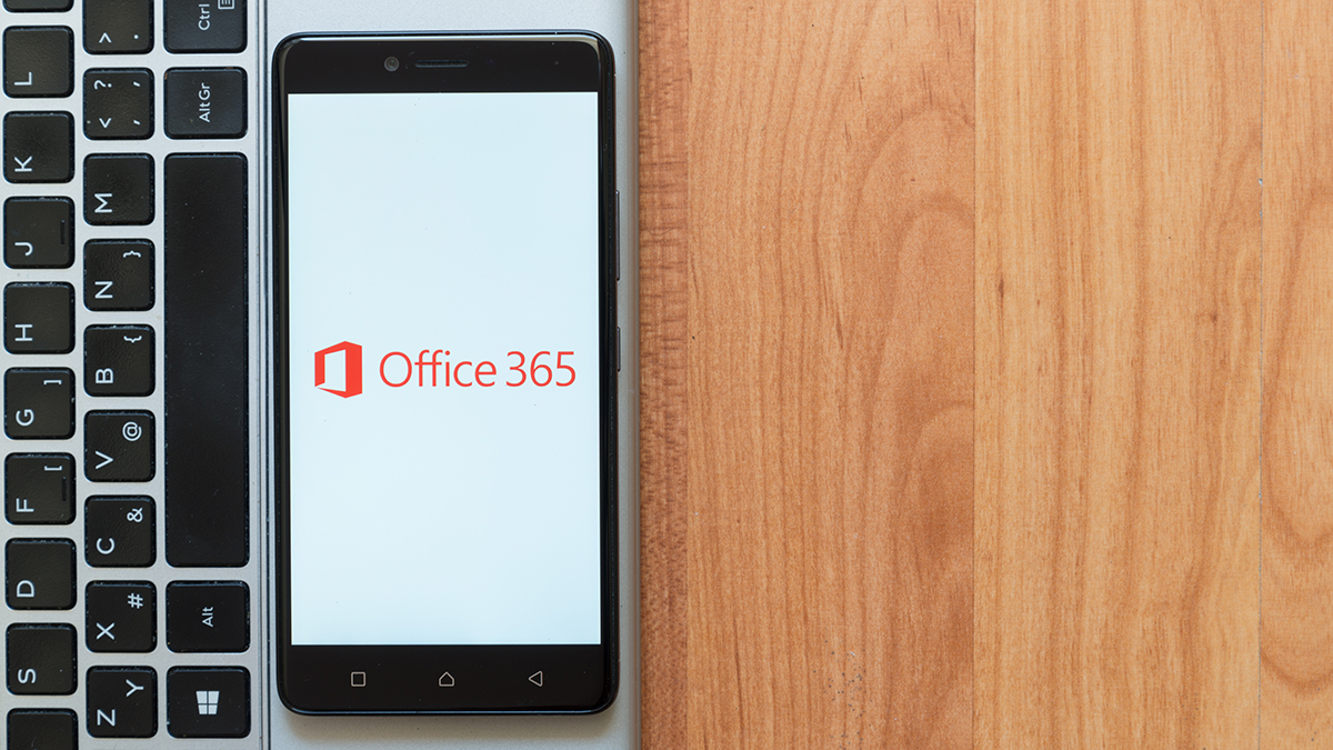 Office 365 on a mobile phone between a keyboard and a wooden desk