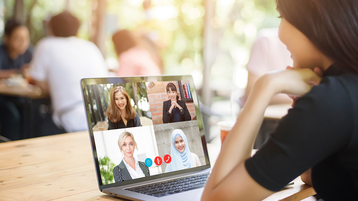Young Woman is looking at her computer screen while business meeting through video conferencing application