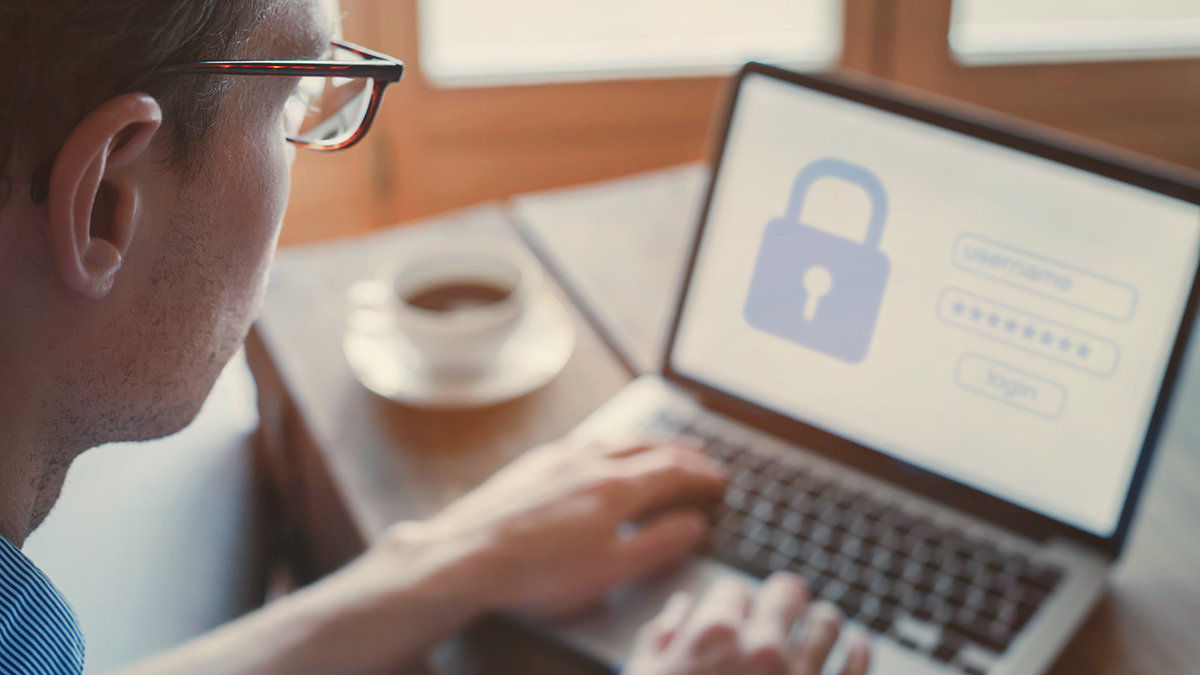 Man with glasses typing login and password on laptop at a wooden table with a cup of coffee illustrates secure computer access.