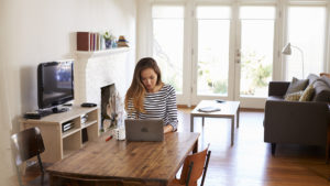 Young woman in a striped shirt working on her laptop on a wooden dining table in her home with her living room in the background.